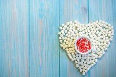 Kaffekoppen mycket av godisar sänker lägger på lantligt ljus - blå träbakgrund Hjärtadiagram som göras från marshmallower Arkivbild