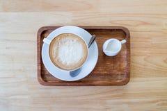 Kaffekoppen och mjölkar på den wood tabellen Royaltyfria Bilder