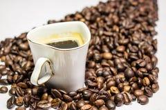 Kaffekoppen omgav kaffebönor i form av uppåtriktade pilar Royaltyfri Foto