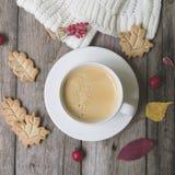 Kaffekoppen, stucken halsduk, torkar sida-, kaka-, hagtorn- och barberryfruitson en träbakgrund Hemtrevlig atmosfär för begrepp m arkivbild
