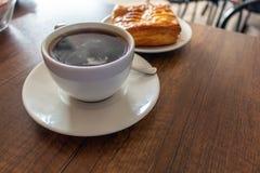 Kaffekoppen tjänade som på en tabell bredvid en ananaskaka royaltyfria foton