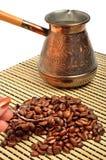 Kaffekruka, kaffe på bordduken och en hand som rymmer en teaspo Royaltyfria Bilder