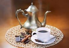 Kaffekruka, kopp kaffe, kryddor och stycken av choklad Arkivbild