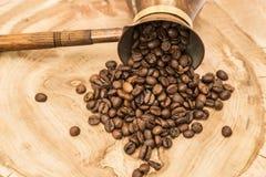 Kaffekruka med kaffebönor arkivfoton