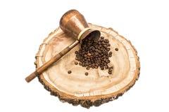 Kaffekruka med kaffebönor på en träbakgrund arkivfoton