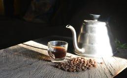 Kaffekruka med kaffekoppen och kaffebönan Arkivbild