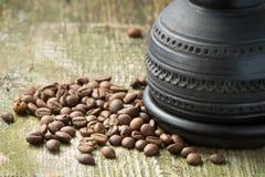 Kaffekruka och bönor på gammal wood bakgrund Arkivbilder