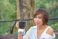 Kaffekrukan i händerna av asiatiska kvinnor royaltyfri foto