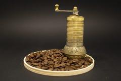 Kaffekvarn med kaffebönor på trätabellen arkivfoto
