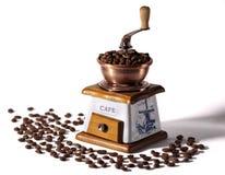 Kaffekvarn- och kaffebönor på en vit bakgrund Fotografering för Bildbyråer