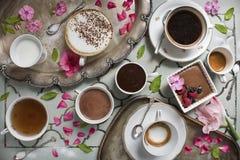Kaffelatte, espresso, te, varm choklad och efterrätt på bakgrunden av magasin för en antik tabell och silveroch gamla skedar royaltyfri foto