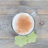 Kaffelatte i den glass koppen med matchakakor, bästa sikt, fyrkantigt format Arkivbild