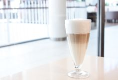 KaffeLatte i exponeringsglas med stort vitt skum arkivfoto