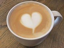 Kaffelatte med mjölkar skum som planläggs som hjärtaform Royaltyfri Bild