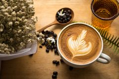 KaffeLatte mjölkar för skedkaffe för den kräm- blomman träträ för bakgrund för bönan royaltyfri foto