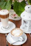 Kaffelatte och cappuccinokafeterian arbeta i trädgården tabellen Royaltyfri Bild