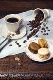 Kaffelynne: kopp kaffe, kaffebönor och mångfärgad macaro Royaltyfria Bilder
