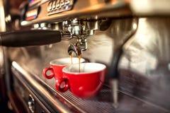 Kaffemaskin som förbereder nytt kaffe och häller in i röda koppar på restaurangen, stången eller baren arkivbilder
