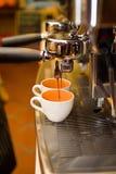 Kaffemaskinen förbereder espresso in till exponeringsglas Arkivbild