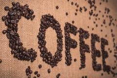 Kaffeord med kaffebönor royaltyfria bilder