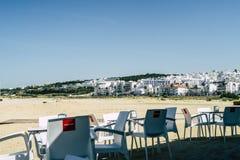 Kaffeställe med den vita stolar och tabellen i en liten stad i sydliga Spanien, på sjösidan av det medelhavs- royaltyfri bild