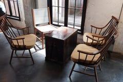 Kaffetabell och stolar nära fönster med vindstil royaltyfria foton