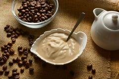 Kaffeyoghurt i den vita bunken med kaffebönan omkring arkivfoton