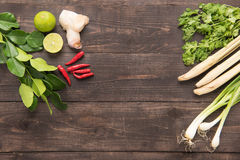 Kaffir lime leaves, coriander or cilantro, Ginger, lemon, lemon. Grass, red chilli and green onions on wooden background. Overhead view Royalty Free Stock Photos