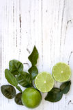 Kaffir Lime Leaves and Fruit Food Background. Kaffir lime leaves and cut and whole fruit, over distressed white timber.  Overhead view Stock Image