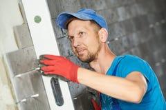 Kaflarz kontroluje poziom dachówkowa panel powierzchnia w sala zdjęcie stock
