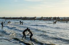 Kafountine, Senegal - 26 de noviembre de 2013: Vuelta de los pescadores en barcos de madera en la playa en Casamance Imagen de archivo libre de regalías