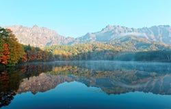 Kagami艾克早晨光的镜子池塘惊人的秋天湖风景与五颜六色的秋叶的相称反射 免版税库存图片