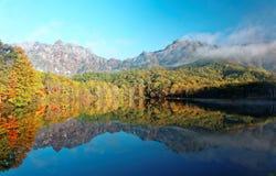 Kagami艾克早晨光的镜子池塘惊人的秋天湖风景与五颜六色的秋叶的相称反射 免版税图库摄影