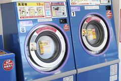 Row of industrial washing machines. KAGAWA, JAPAN - OCTOBER 29, 2018: Row of industrial washing machines in a public laundromat stock image