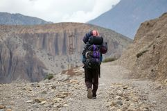 Hired porters who are hired to carry a backpack of tourists, It goes in the Himalayan mountains of the Kingdom Mustang. Nepal. Stock Image
