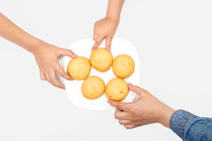 Kahk El Eid. Hands take cookies of El Fitr Islamic Feast from a plate Royalty Free Stock Photo