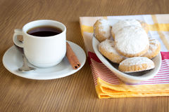 Kahk El Eid with tea. Kahk El Eid - Feast Cookies - with cup of tea on a wooden table Stock Image