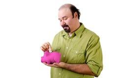 Kahl werdend Mann, der Geld in Sparschwein einsetzt Stockfotografie