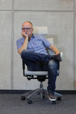 Kahl werdend Mann des Mittelalters mit schlechter Sitzposition der Brillen auf Stuhl im Büro Stockbild