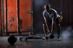 Kahler charismatischer Athlet, der Hocken mit Gewichten tut Stockbild