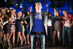 Kahler Kerl mit den Händen in den verschiedenen Richtungen und in dreizehn jungen Leuten Stockbild