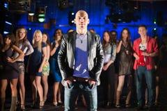 Kahler Kerl mit dreizehn jungen Leuten im Hintergrund Stockbilder