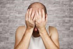 Kahler Mann des Porträts bedeckt sein Gesicht mit seinen Händen und Schreien von der Hoffnungslosigkeit, von der Einsamkeit und lizenzfreies stockfoto