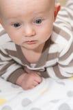 Kahles Baby, das unten mit Big Blue-Augen schaut Stockbild