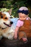 Kahles Baby im Schmutz mit Hund stockfotografie