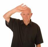 Kahlköpfiger Mann, der Augen abschirmt stockfotos