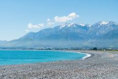 Kaikoura strand som buktas med bergbakgrund Royaltyfria Foton