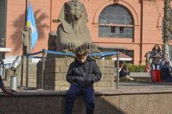 KAIR EGIPT, LISTOPAD, - 22, 2013: Chłopiec obsiadanie blisko sfinksa Egipski muzeum narodowe Fotografia Stock