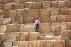 Kairo, ÄGYPTEN - 22. April 2015, das Mädchen, das auf den alten Steinen der ägyptischen Pyramiden in Giseh, am 22. April 2015 in  Stockfoto