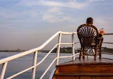 Kairo Egypten April 6 2012: Man som kopplar av på pilbågen av segelbåten på flodNilen i Kairo Arkivbilder